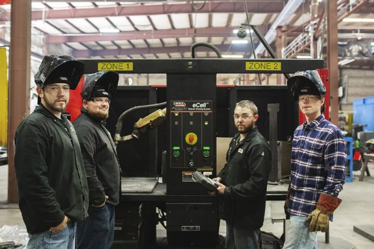 Instructor and three welders in front of the robot