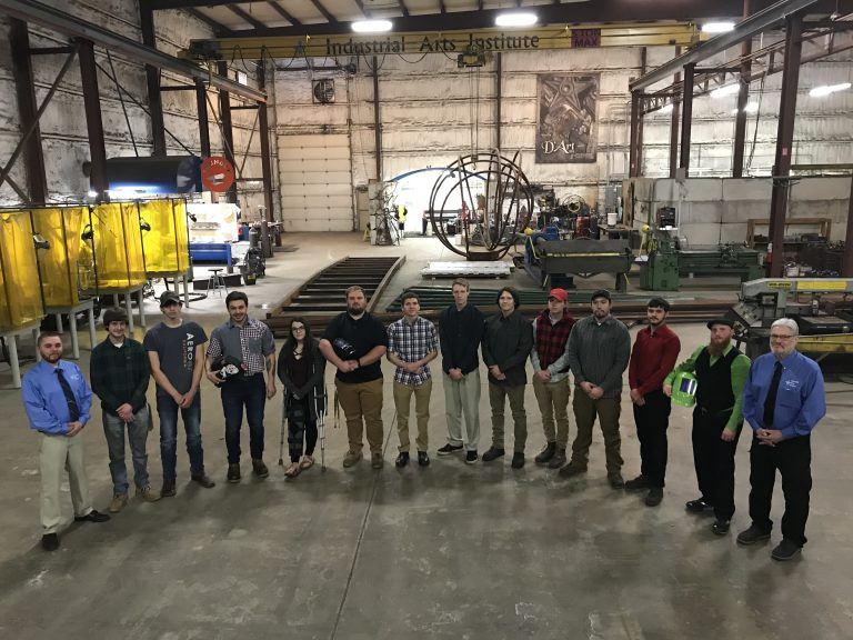 Class of welders and instructors posing in lab