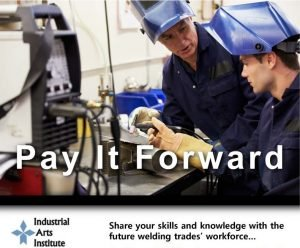 """A welding instructor helping a student, featuring a message """"pay it forward"""""""