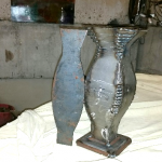 Two vases made of metal, showing welds